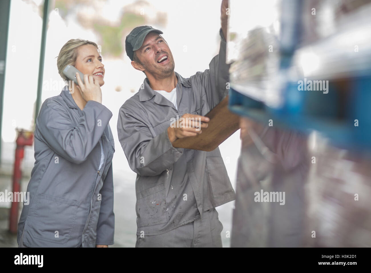Factory supervisors with clipboard checking pallets at packaging factory - Stock Image