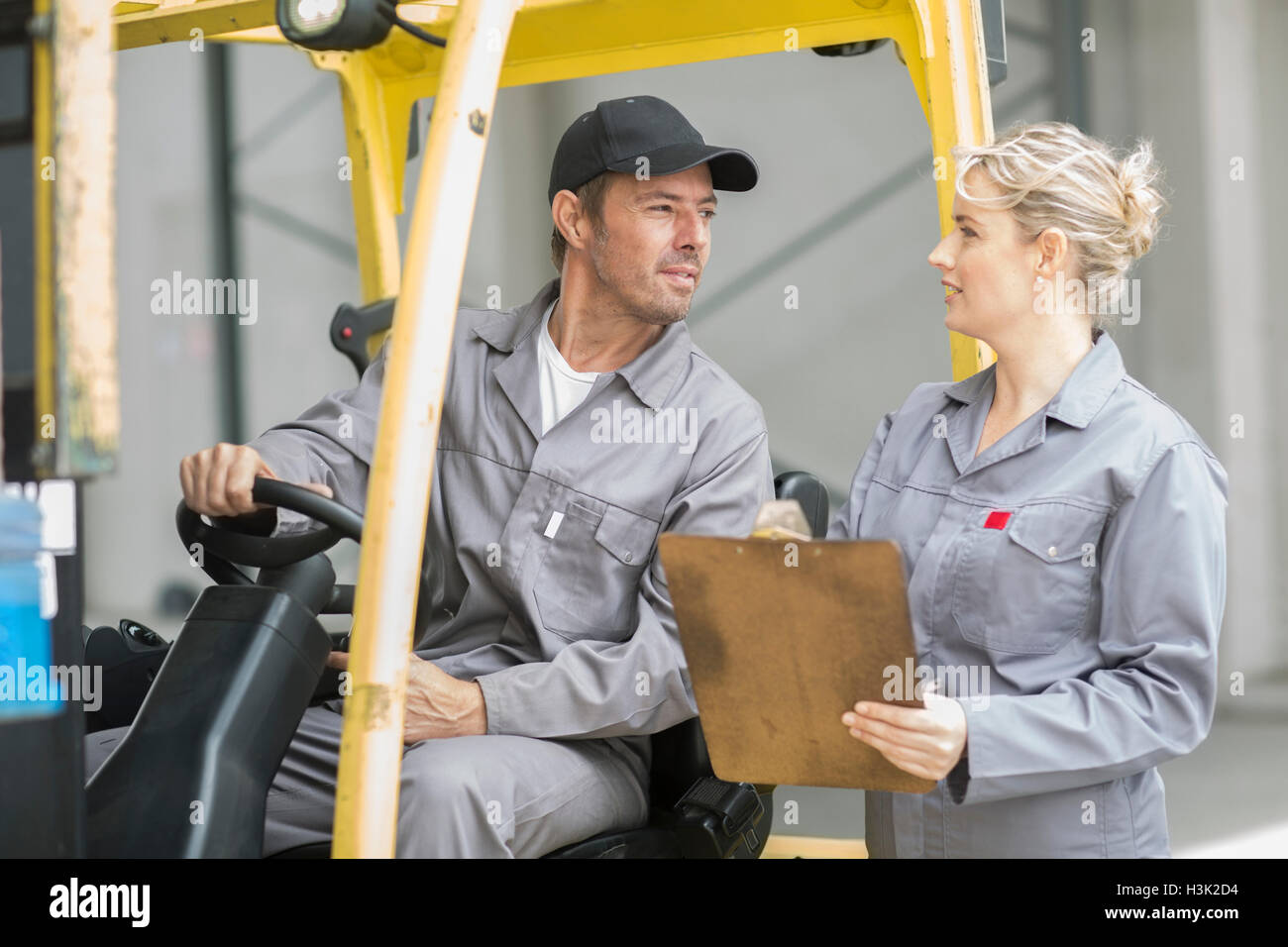 Factory supervisors with clipboard talking to forklift driver at packaging factory - Stock Image