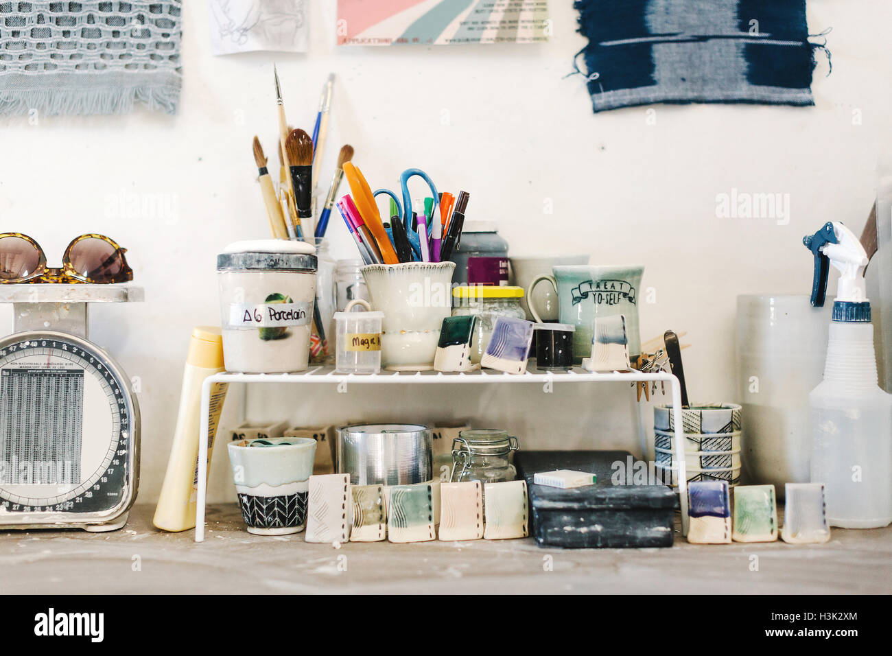 Assortment of art materials and tools in pottery studio - Stock Image