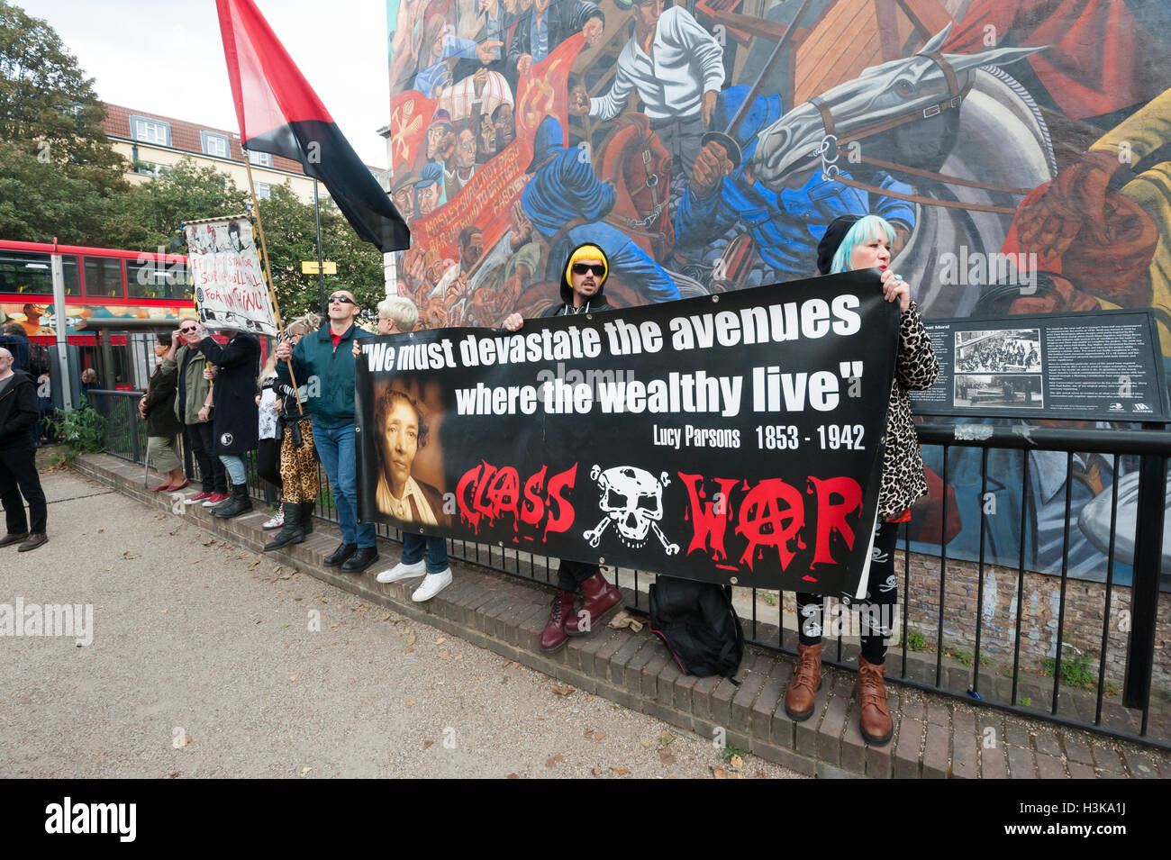 London, UK. 9th October 2016. Class War  banners in front of the Cable Street mural as marchers arrive. Class War - Stock Image