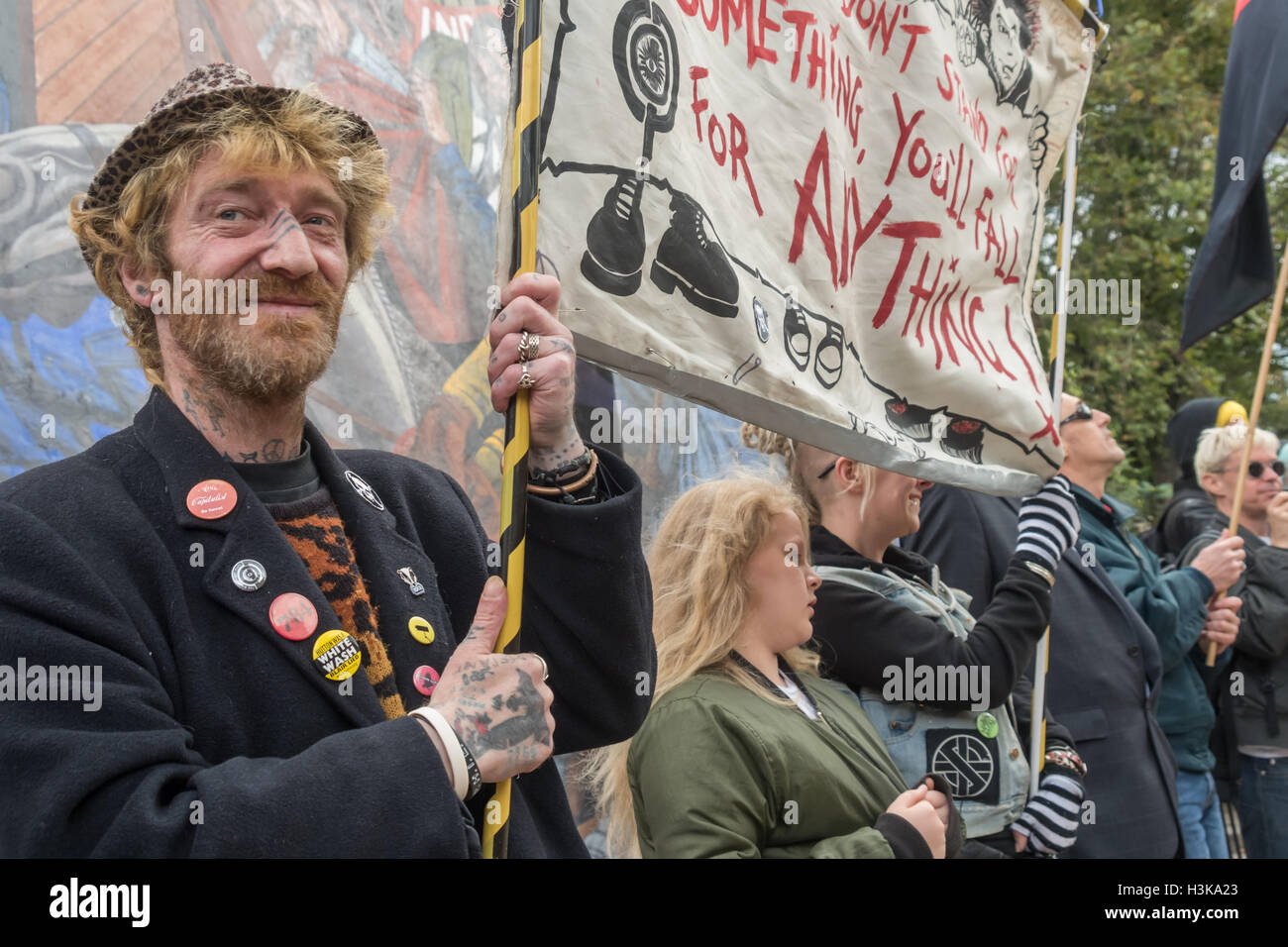 London, UK. 9th October 2016. Class War with banners in front of the Cable Street mural as marchers arrive. Class - Stock Image