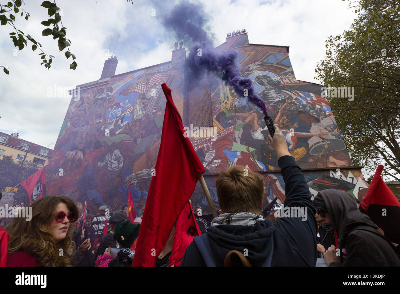 London, UK. 9th October 2016. Anarchists and anti-fascists let off smoke flares at the Cable Street Mural during - Stock Image