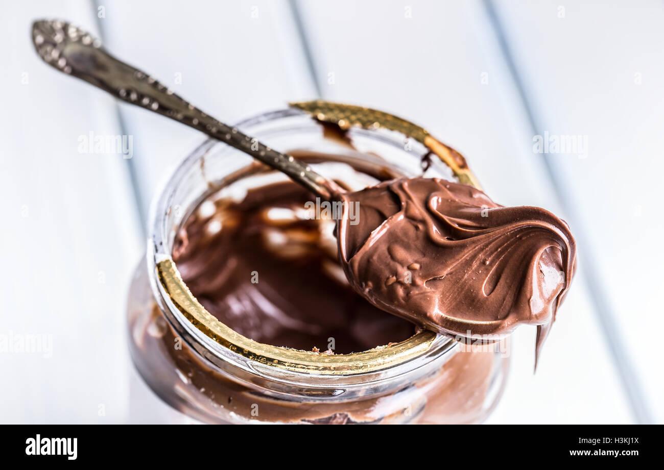 Chocolate spread in spoon. A jar of hazelnut chocolate spread. - Stock Image