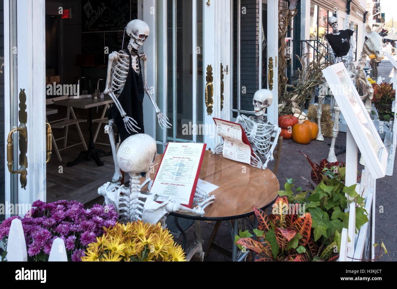 Halloween skeletons having lunch in a Little Italy restaurant in New York City - Stock Image