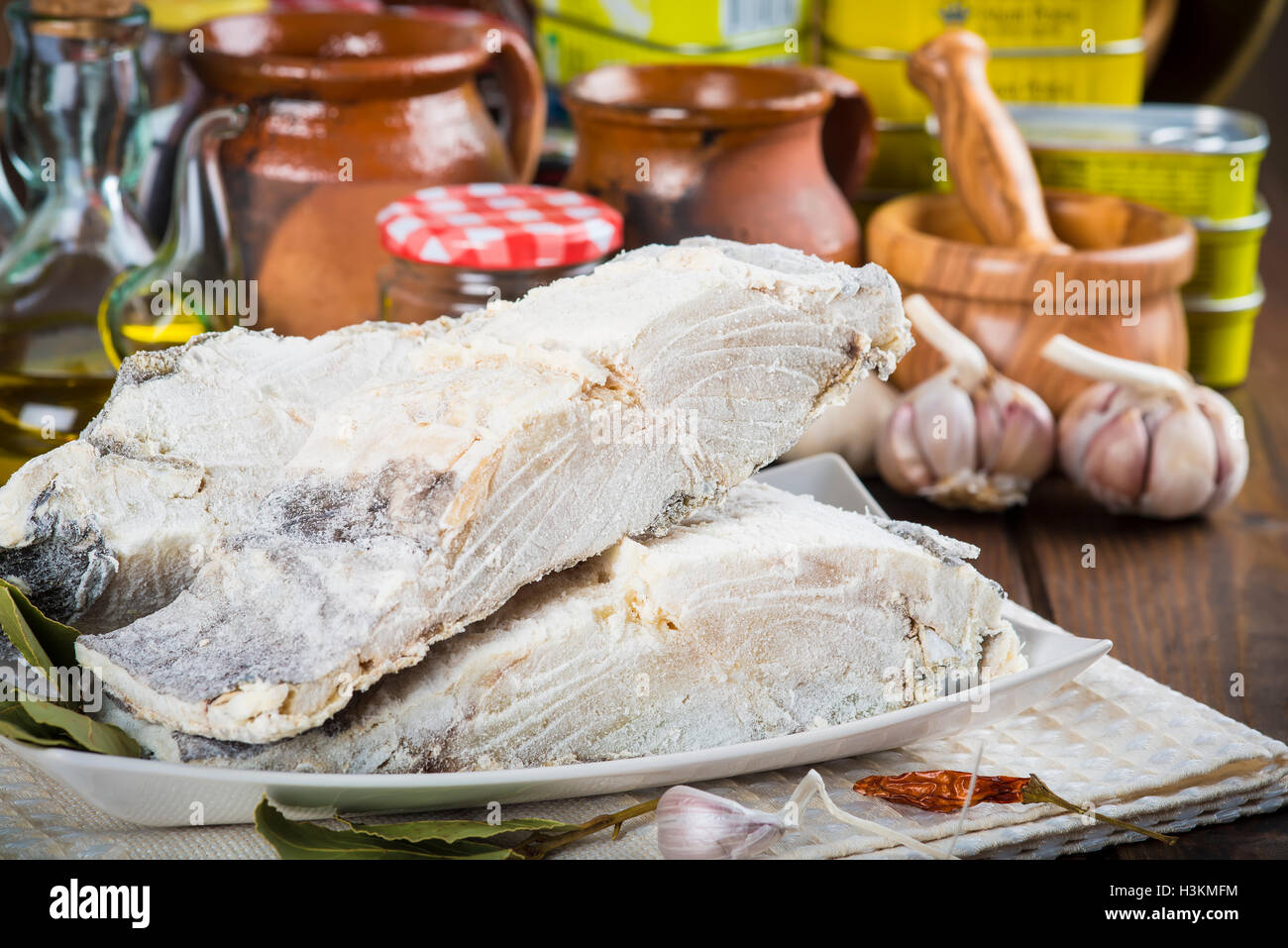 Salted cod cut with ingredients and utensils on the table of the kitchen for cooking - Stock Image