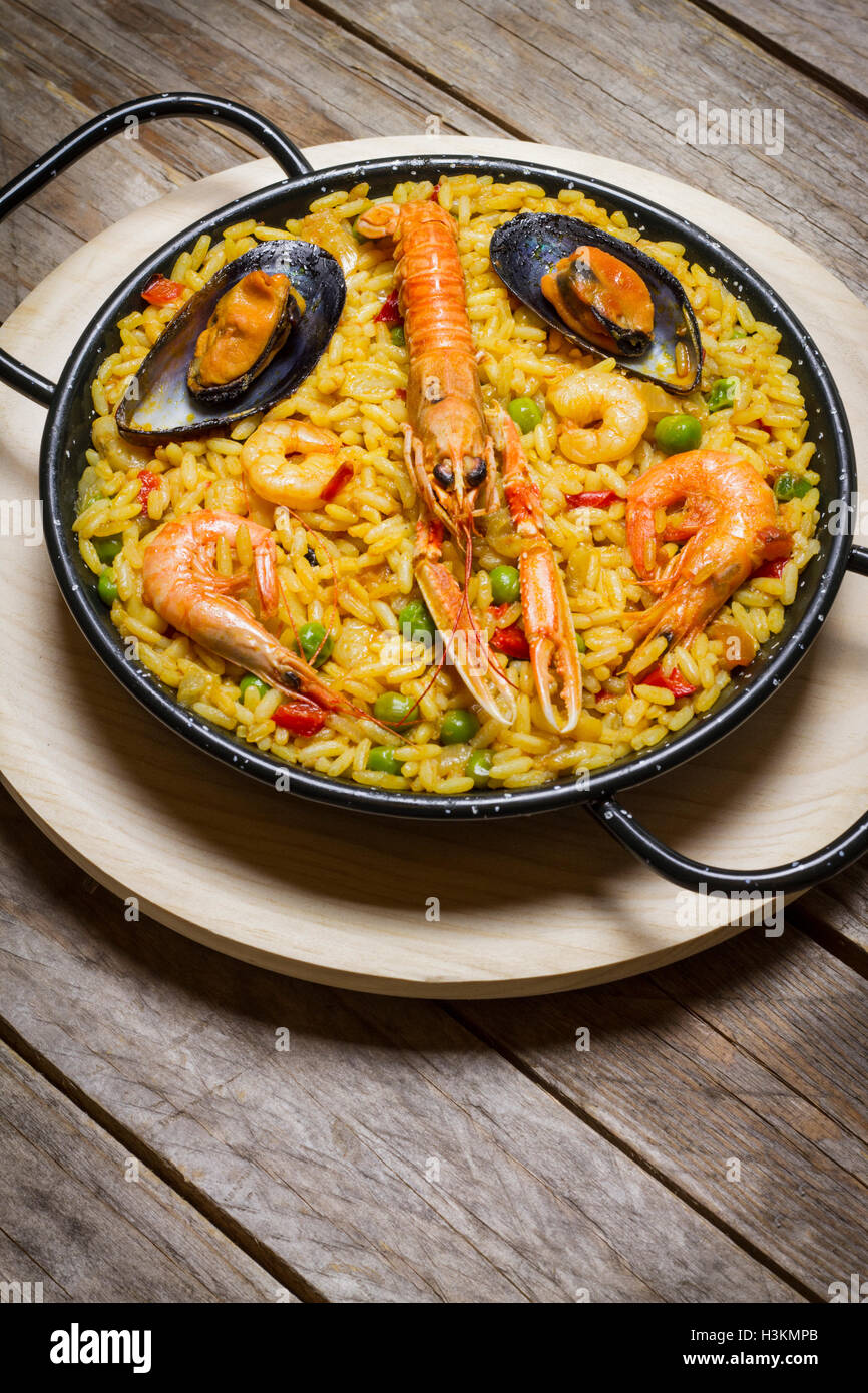 Spanish paella on a wooden table, portrait orientation - Stock Image