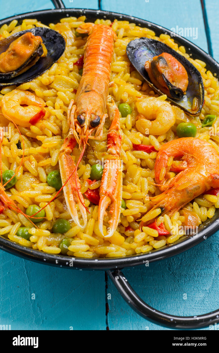 Spanish paella on a blue wooden table - Stock Image