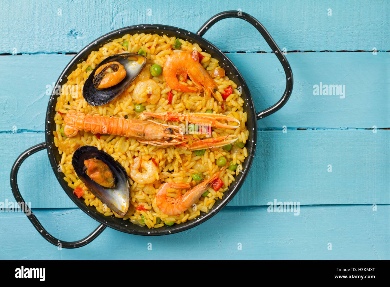 Spanish paella on a blue wooden table with copy space on the right - Stock Image