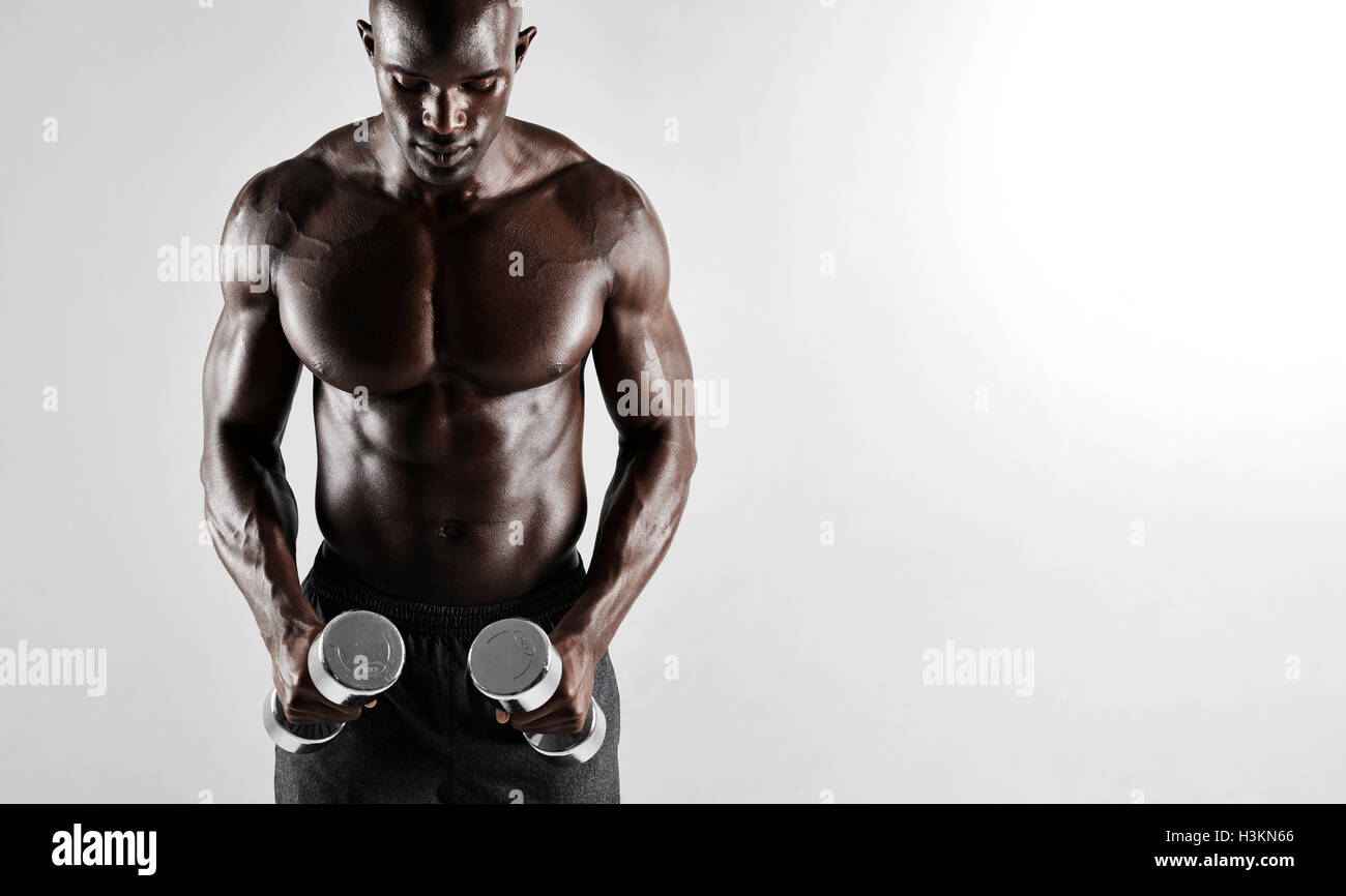 Shot of muscular young african man exercising with dumbbells. Fit black male model with dumbbells over grey background. Stock Photo