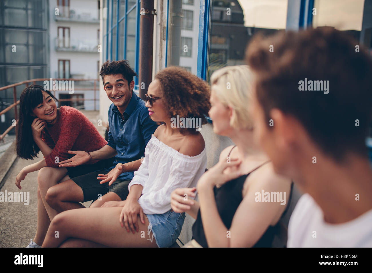 Multiracial group of friends sitting in balcony. Young people relaxing outdoors in terrace. - Stock Image