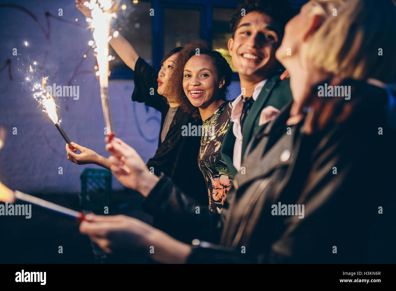 Group of friends enjoying out with sparklers. Young men and women enjoying new years eve with fireworks. - Stock Image