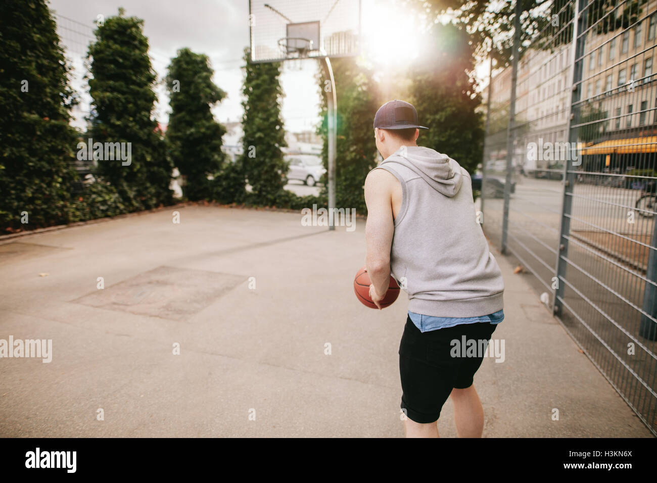 Rear view shot of a streetball player playing basketball. Young guy playing basketball on outdoor court. - Stock Image
