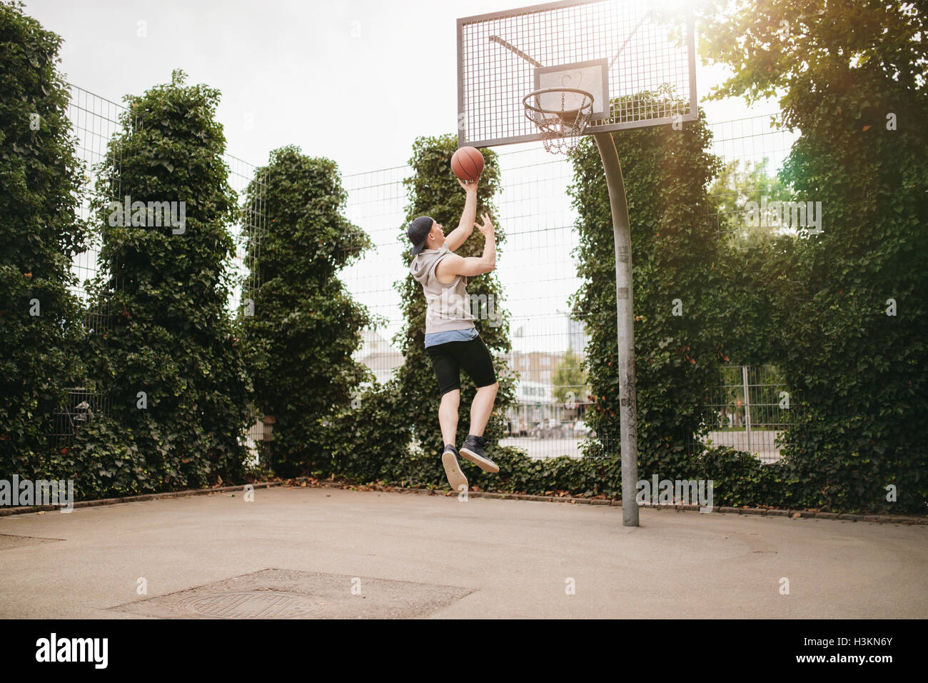 Young man jumping and dunking basketball into hoop. Teenage guy playing streetball. - Stock Image