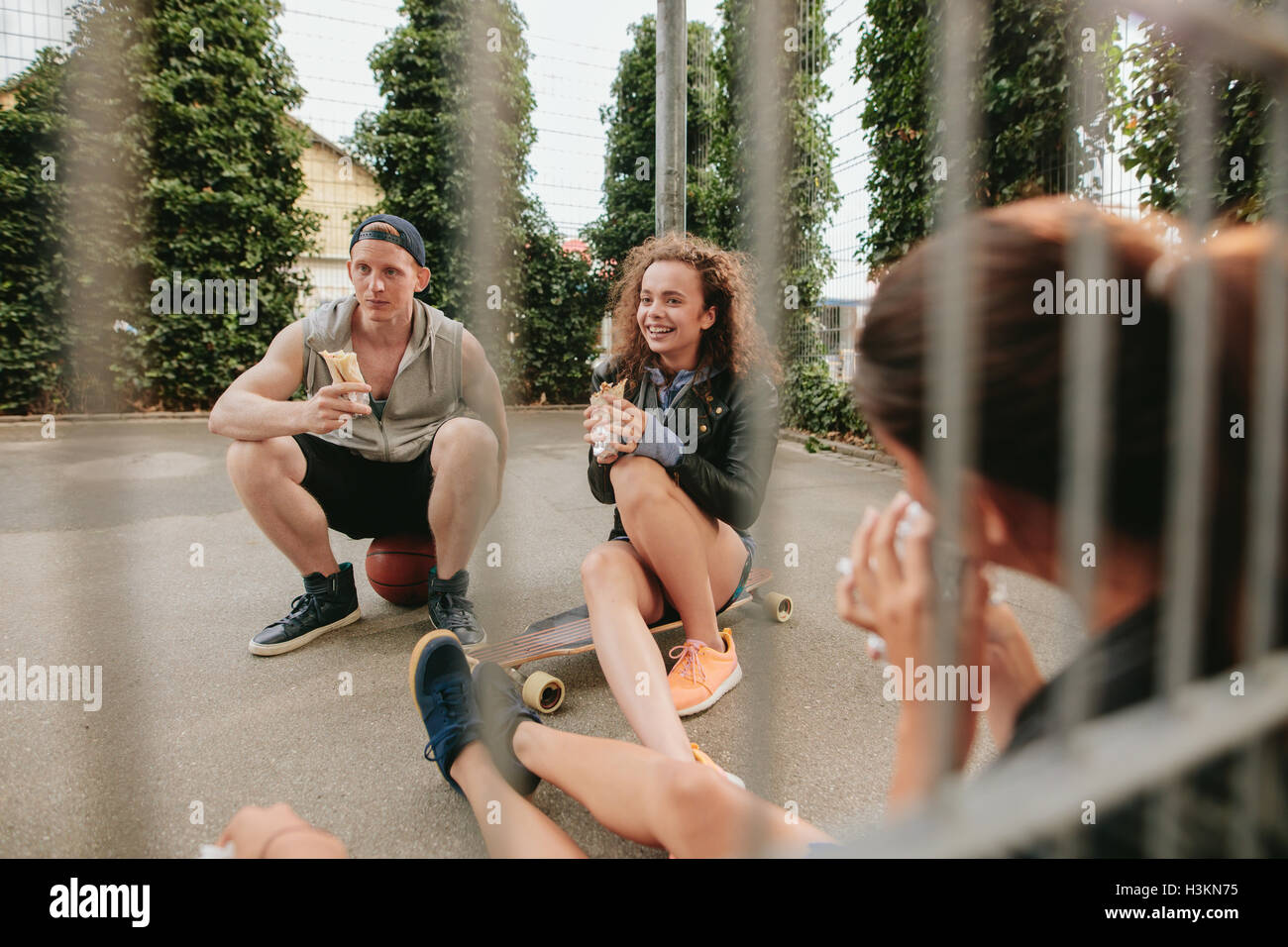Group of friends sitting at outdoor basketball court eating and having fun. Teenagers relaxing basketball court. - Stock Image