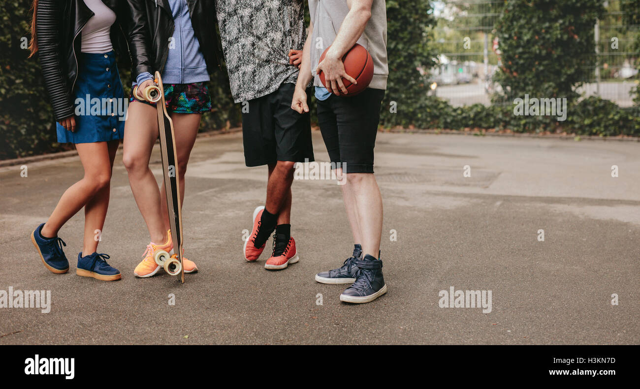 Cropped shot of group of people standing together with basketball and skateboard. Low angle shot with focus on men and women leg Stock Photo