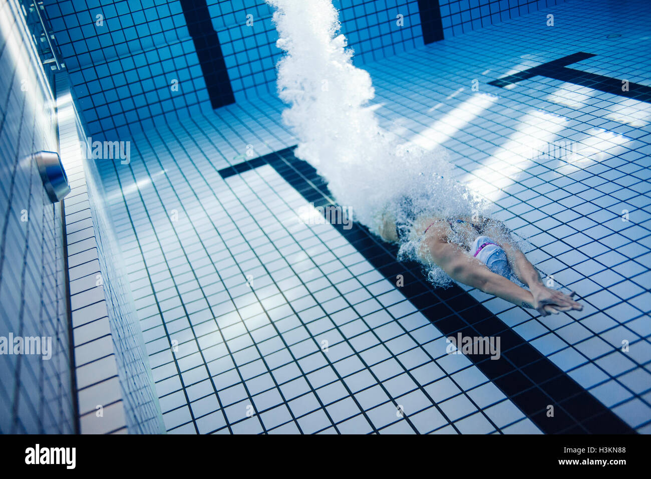 Underwater shot of female swimmer swimming inside pool. Fit young female swimmer training in the pool. - Stock Image