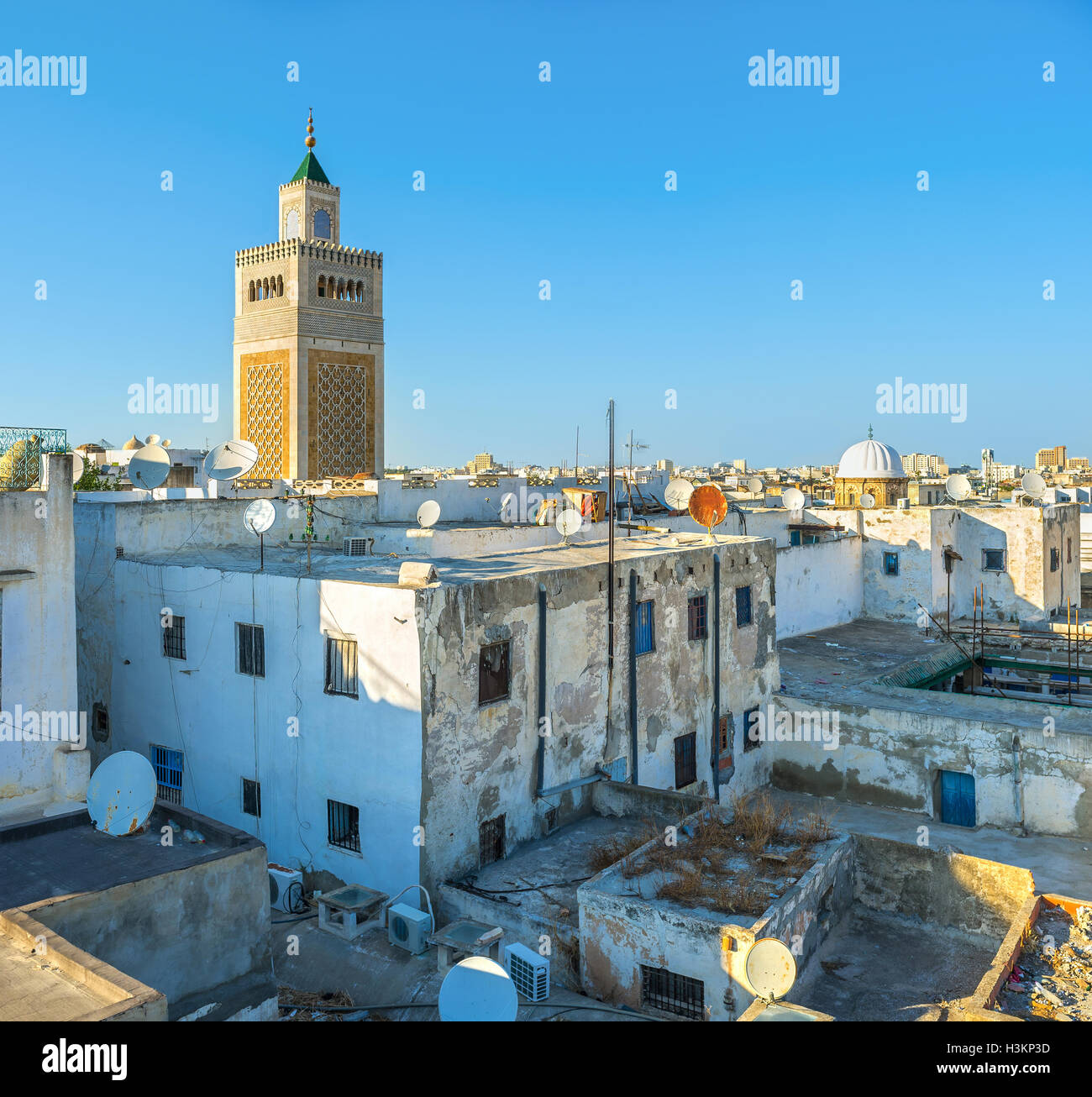 The rectangular minaret of the Great Mosque over the city roofs, Tunis, Tunisia. - Stock Image