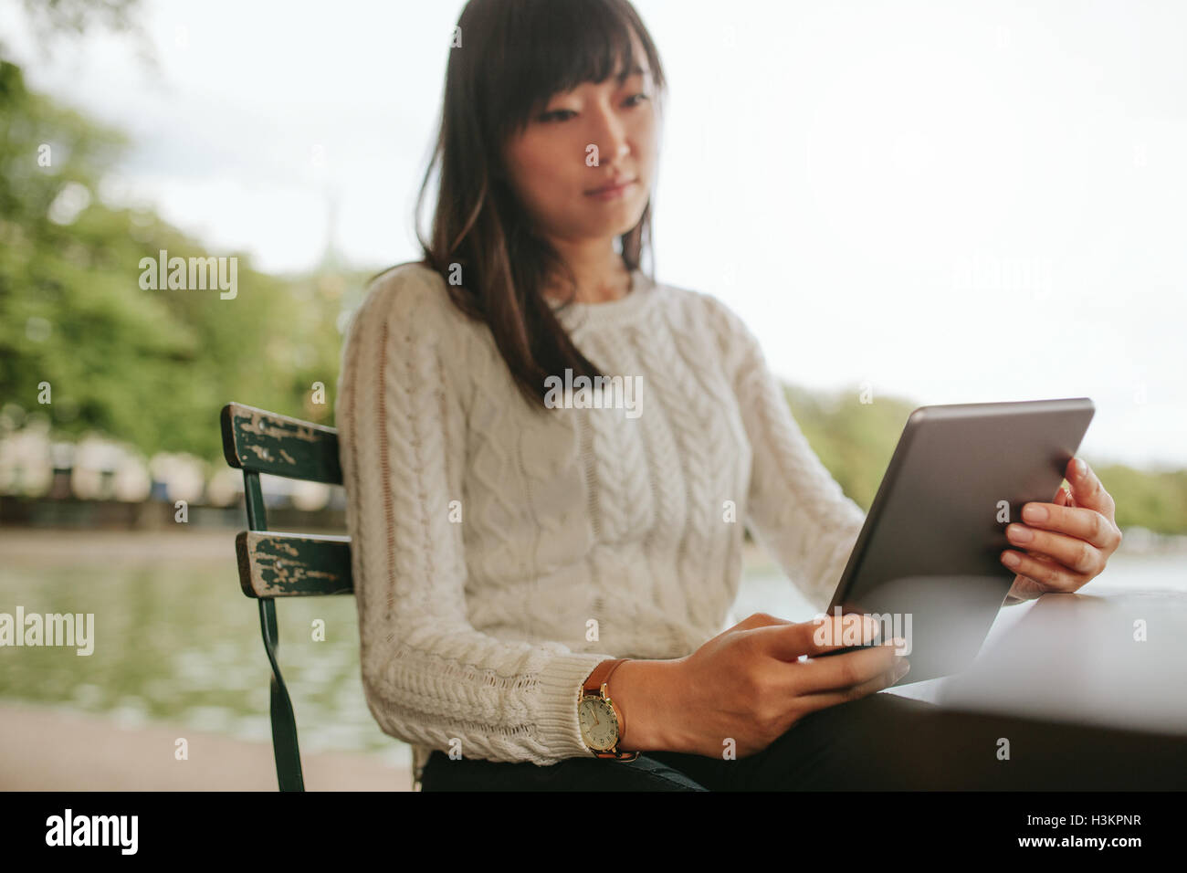 Young woman reading ebook on her digital tablet. Chinese female at outdoor cafe using digital tablet. - Stock Image