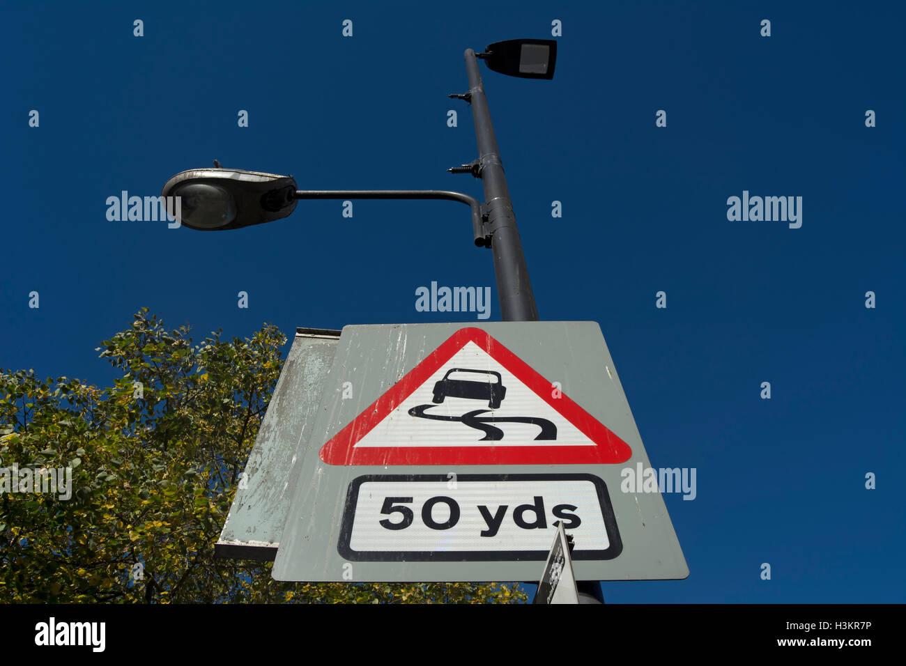british road sign warning of a slippery road surface 50 yards ahead, in hounslow, middlesex, england Stock Photo
