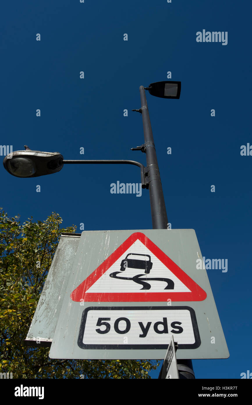 british road sign warning of a slippery road surface 50 yards ahead, in hounslow, middlesex, england - Stock Image