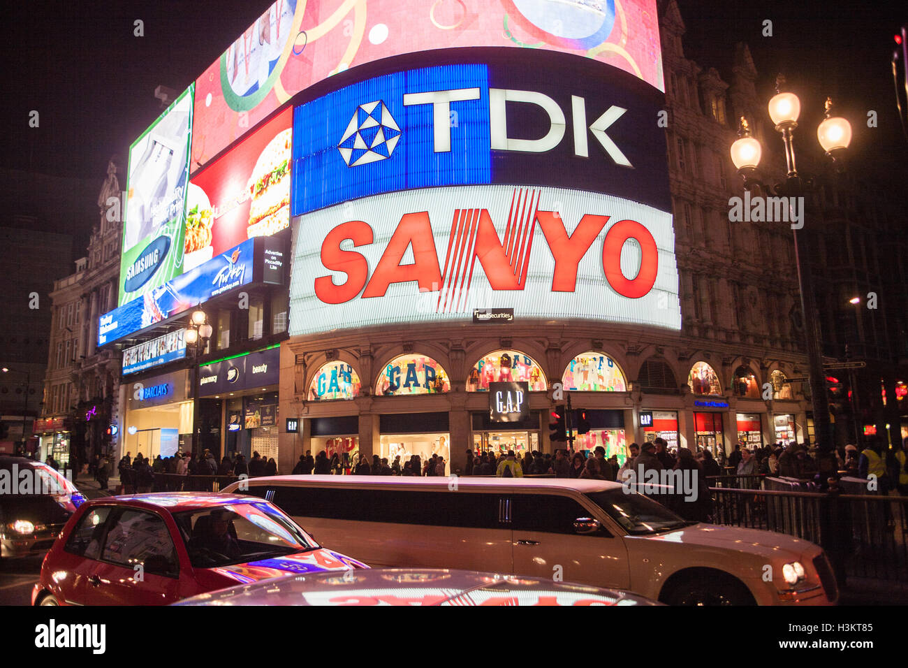 Stretched limo limousine and cars traffic passing neon lights of Picadilly Circus,Piccadilly,London,England,U.K.,Europe. - Stock Image