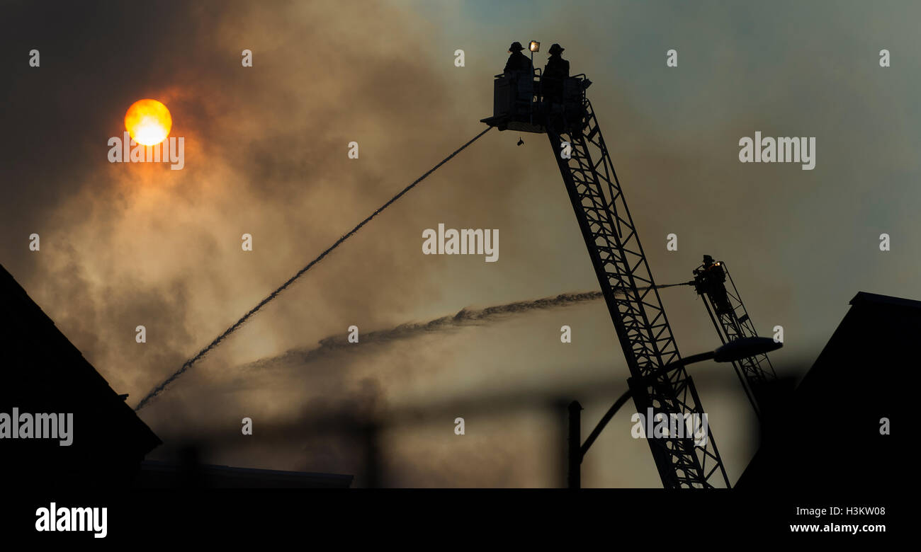A Tower Ladder and aerial ladder pipe play water into a vacant school as the sun rises and shines through the smoke. - Stock Image