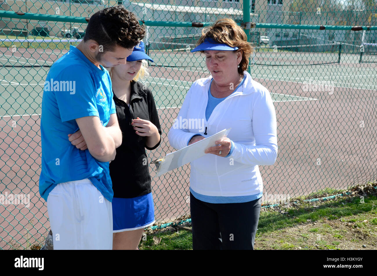 coach talks to teen tennis players about the tennis schedule - Stock Image
