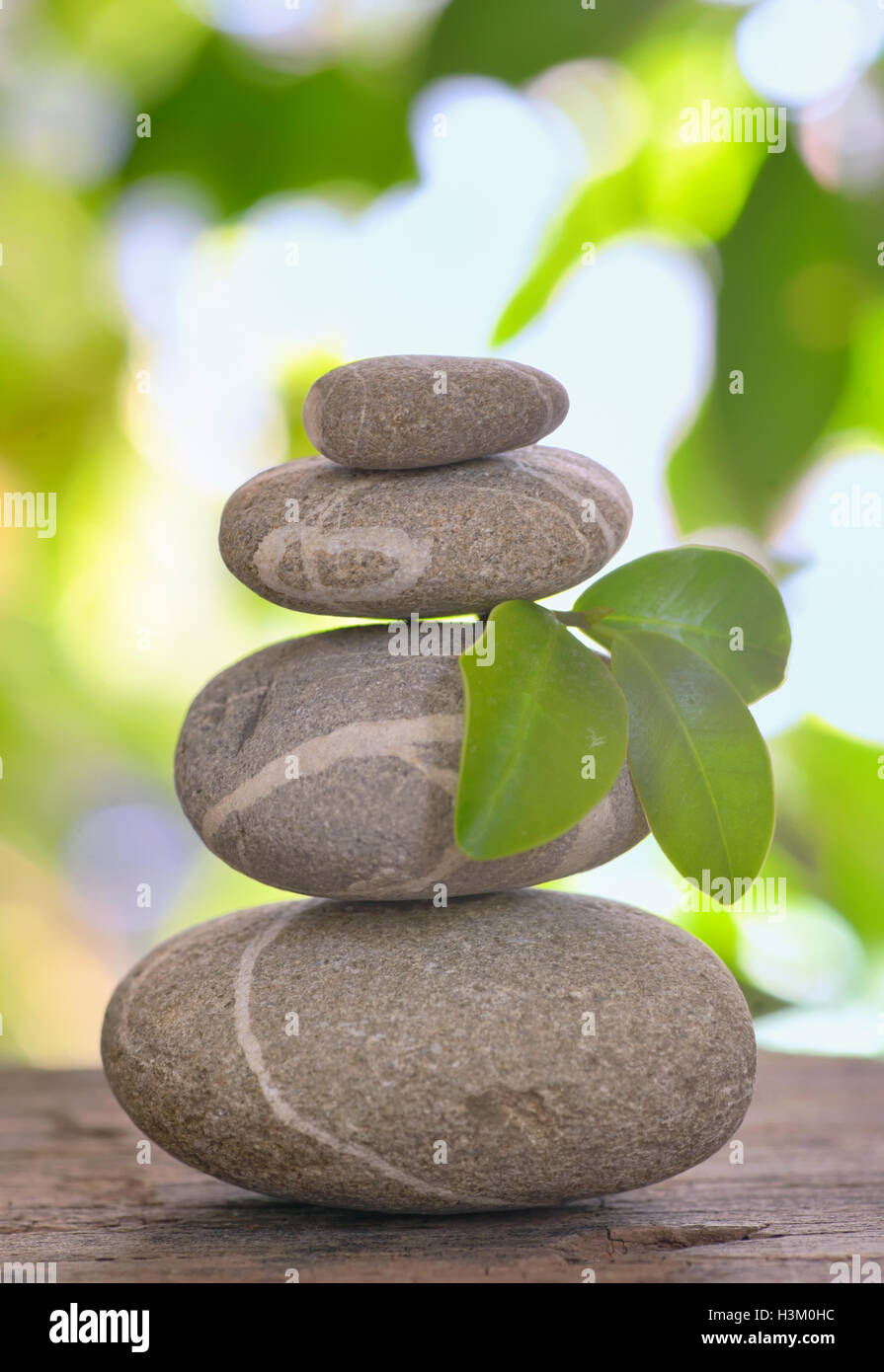 Balanced pebbles isolated on wooden table - Stock Image