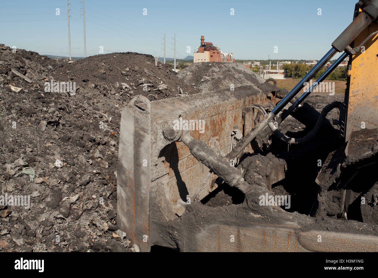 A heap of ash and debris from burned trash at a municipal landfill site. Incinerator in rear generates electricity - Stock Image