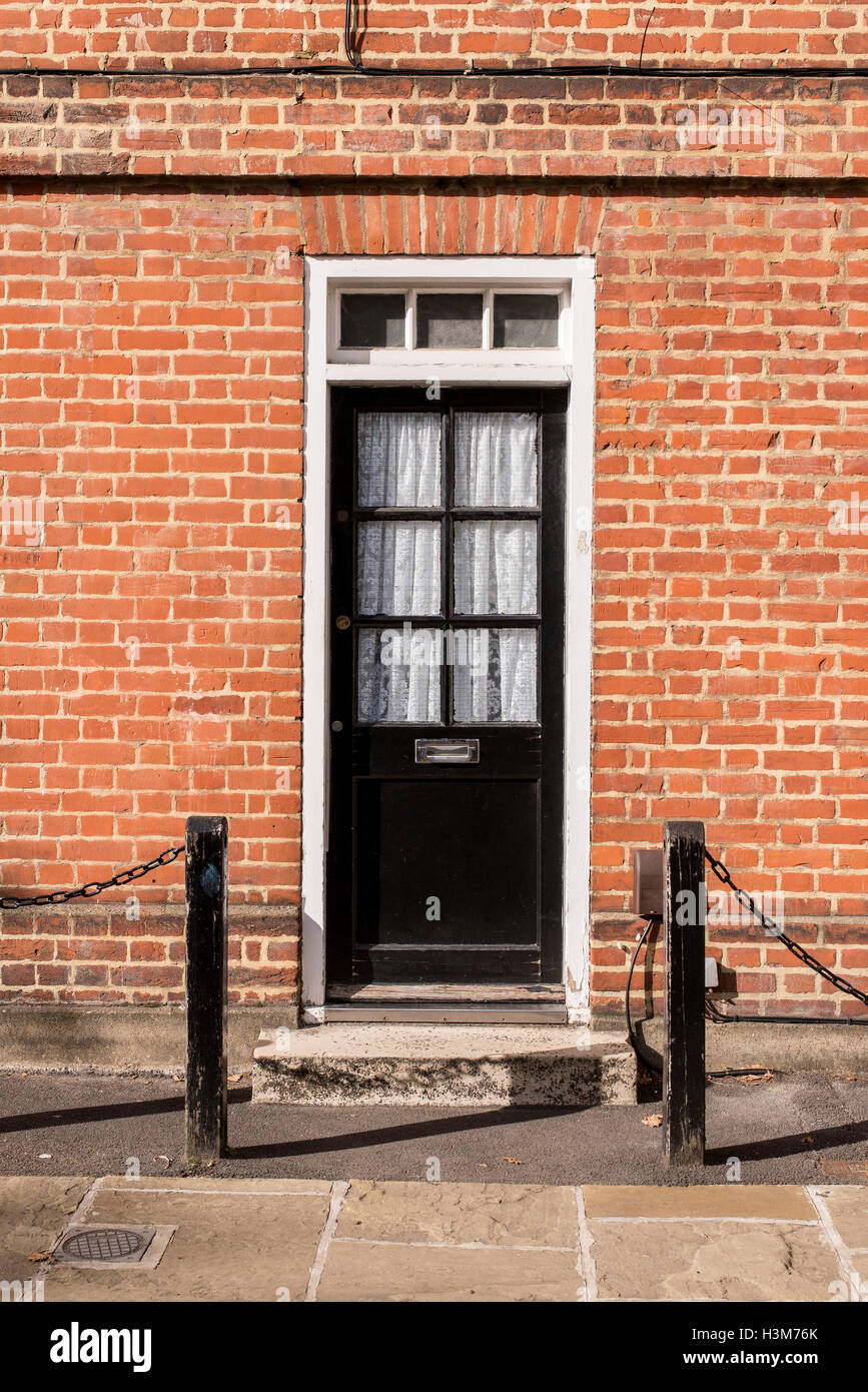 Victorian black external wooden door with glass panels on a classic red brick wall Stock Photo