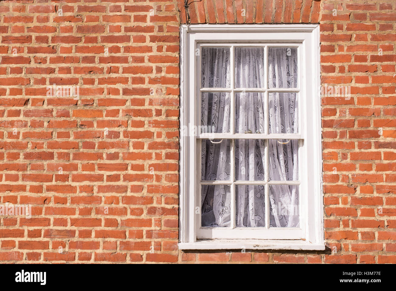 Victorian wooden frame white sash window with glass panels on a classic red brick wall