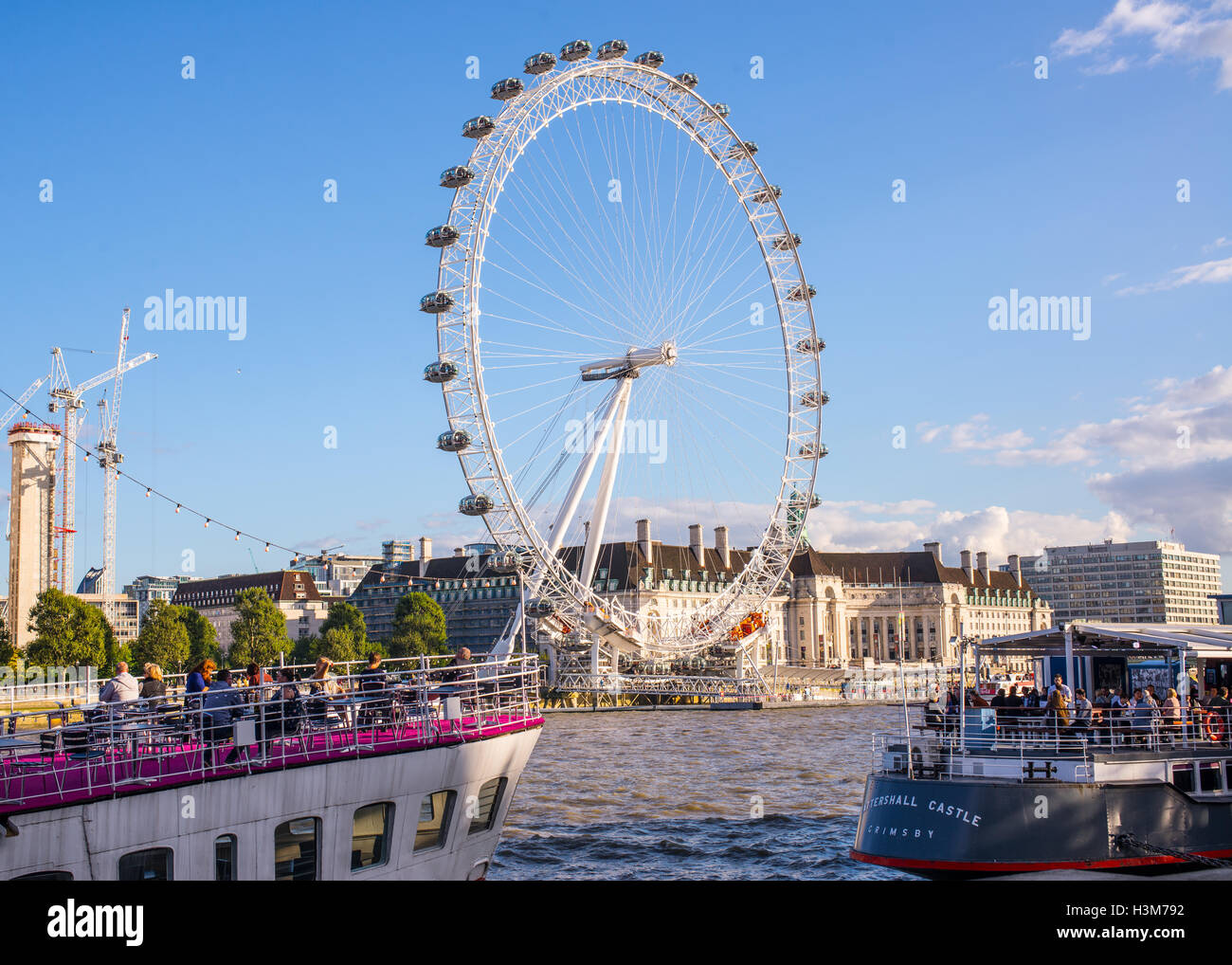 People drinking and eating on boat restaurants under the London Eye while cruising on the Thames - Stock Image