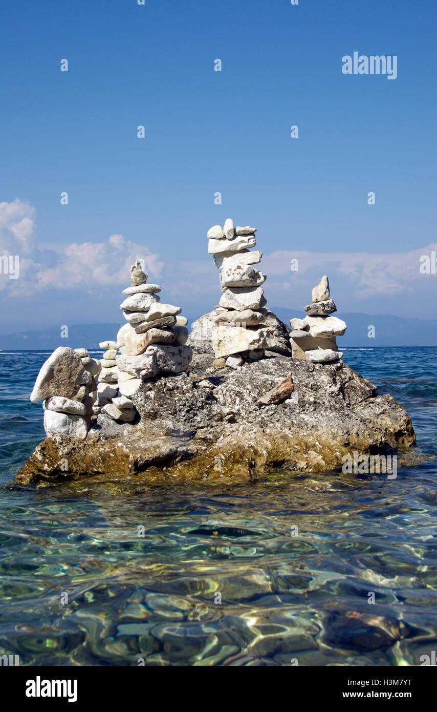 Stone balancing Gaios Harbour Paxos Ionian Islands Greece - Stock Image