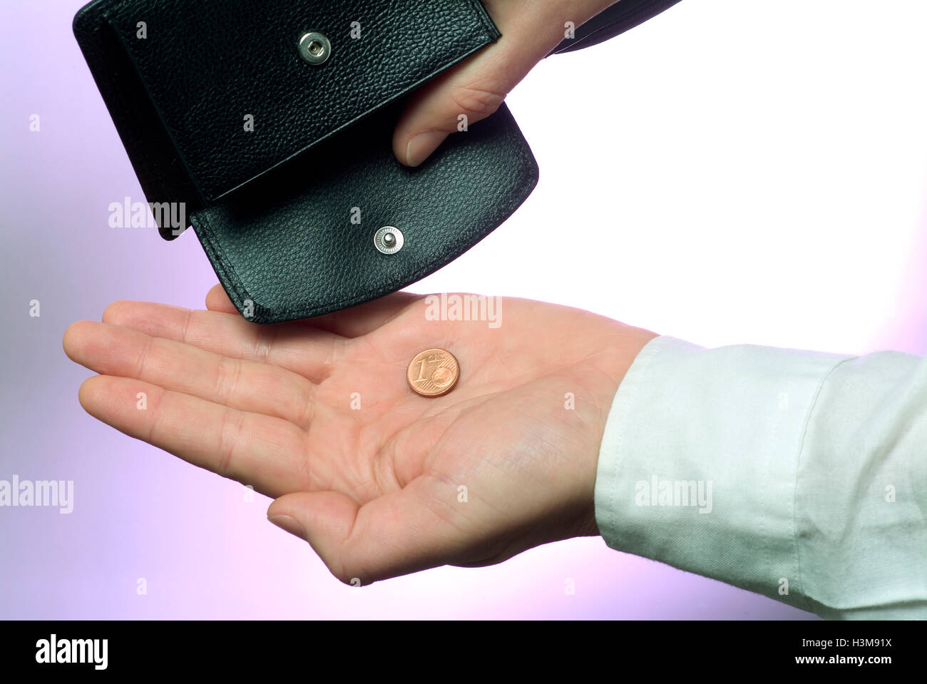 Wallet with hand and one last coin - Stock Image