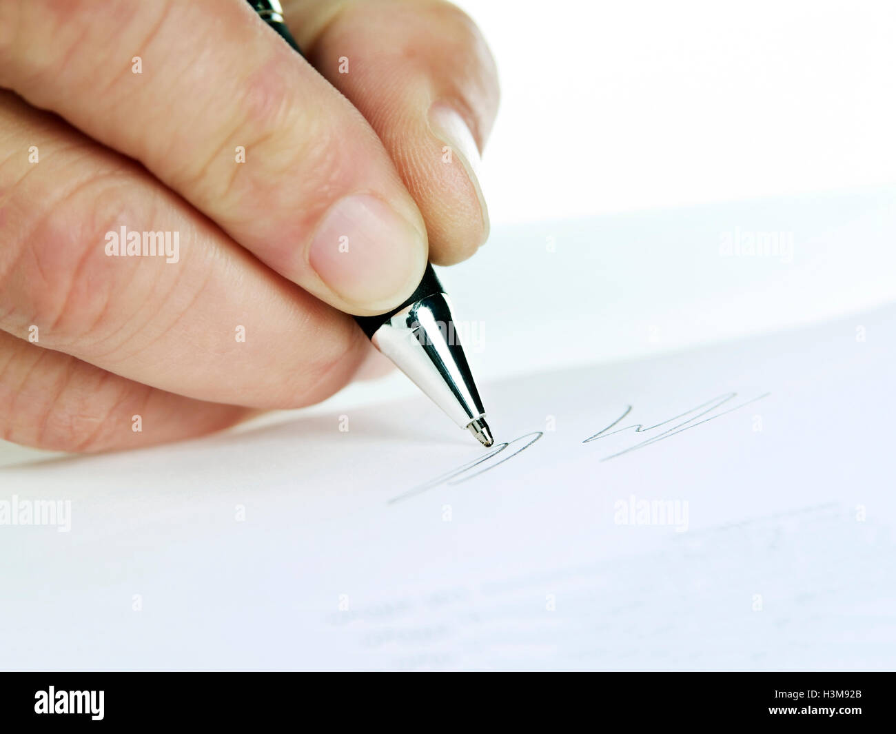 Close-up of a hand while signing - Stock Image