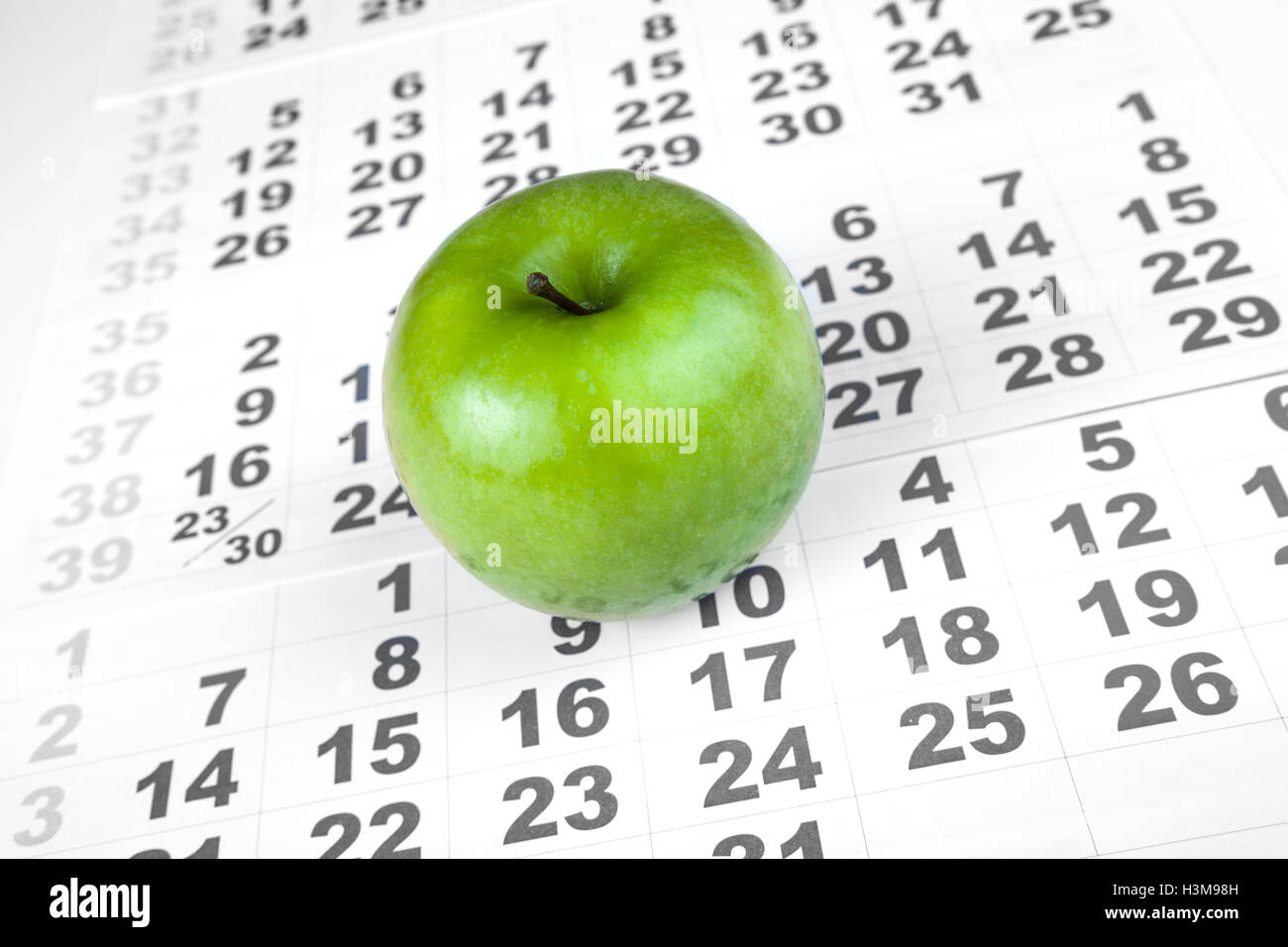 green apple on sheets of wall calendar - Stock Image