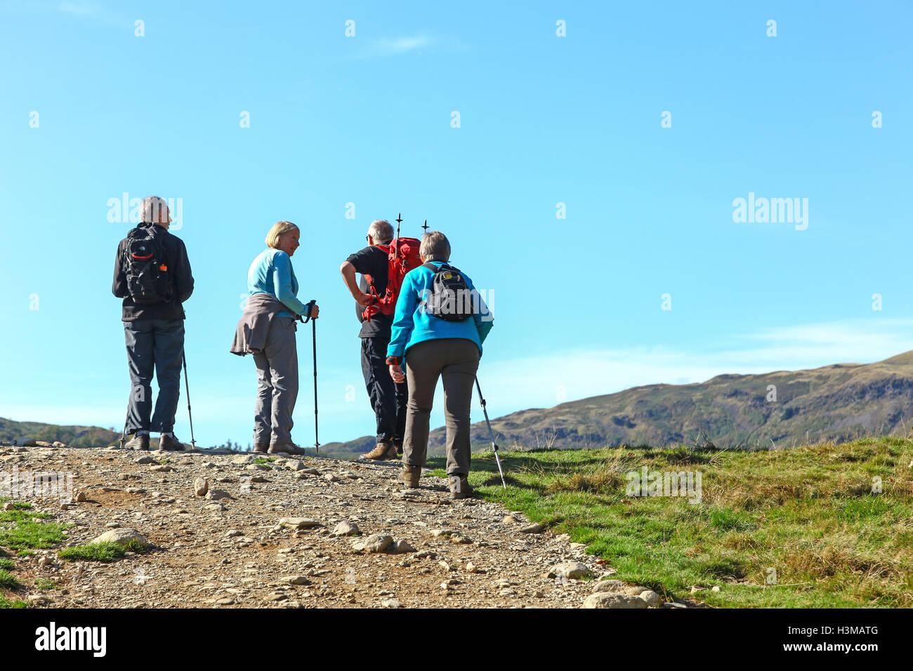 Four elderly walkers reaching the summit of a hill in the English Lake District Cumbria England UK - Stock Image