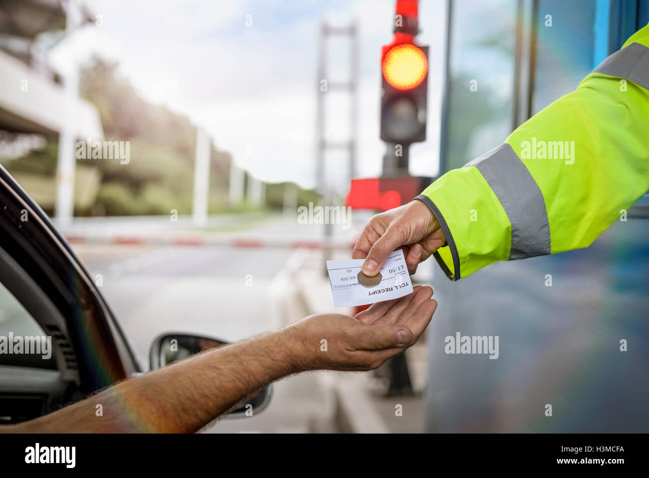 Driver in car paying toll booth at bridge, close up - Stock Image