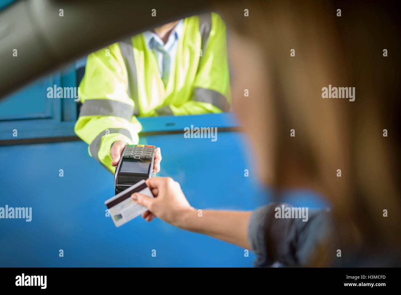 Driver in car paying toll booth using contactless card payment technology, close up - Stock Image