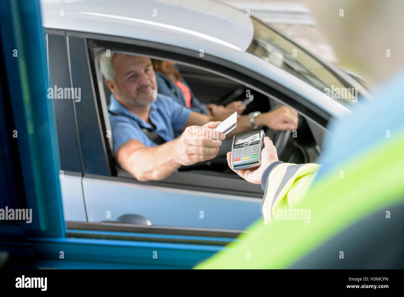 Driver in car paying toll booth at bridge using contactless card payment technology - Stock Image
