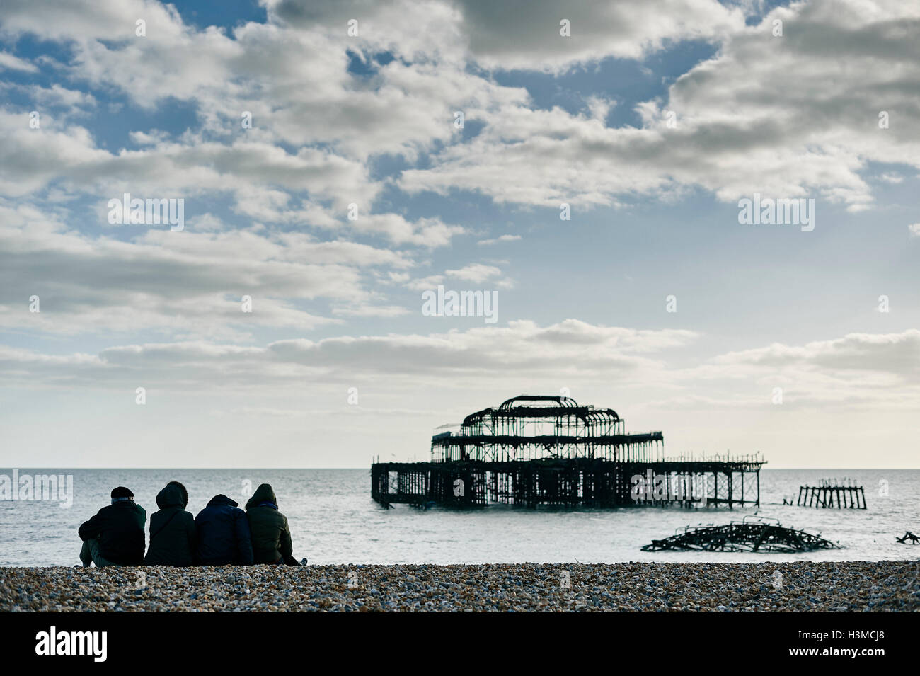 Tourists relaxing on Brighton beach, England - Stock Image