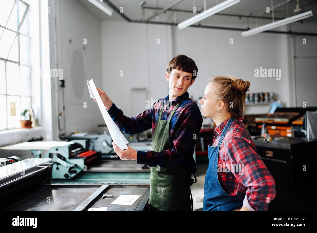 Young male and female craftsperson looking at print in book arts workshop - Stock Image