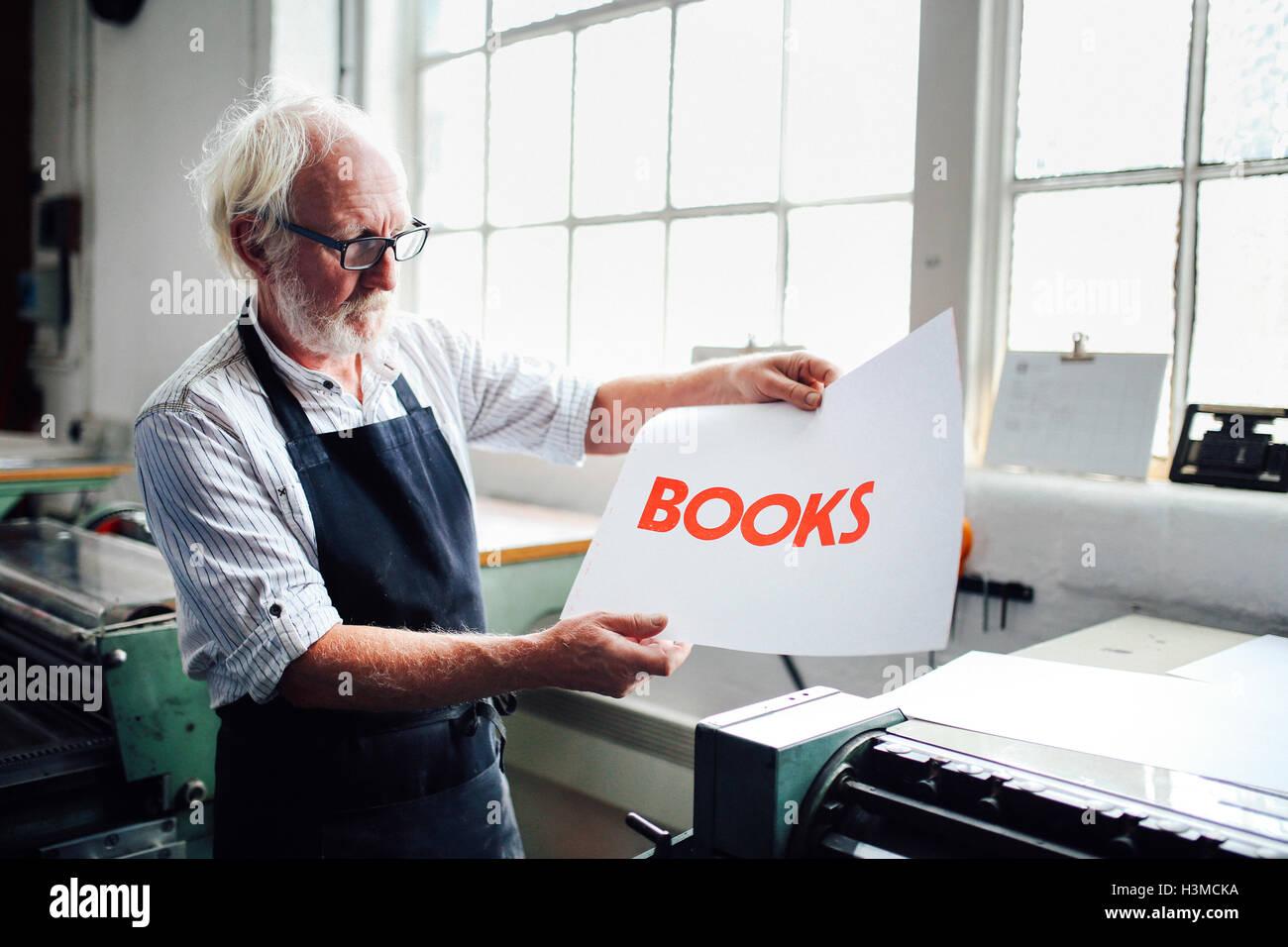 Senior craftsman/technician holding up letterpress print in book arts workshop - Stock Image