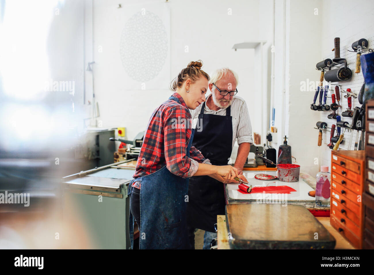 Senior craftsman/technician supervising young woman as she uses ink roller for letterpress printing in book arts - Stock Image