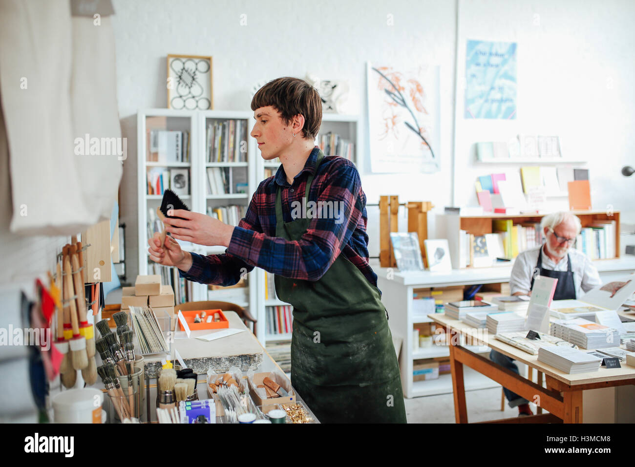 Young craftsman picking up brush and looking at materials in craft shop, with senior man in background - Stock Image