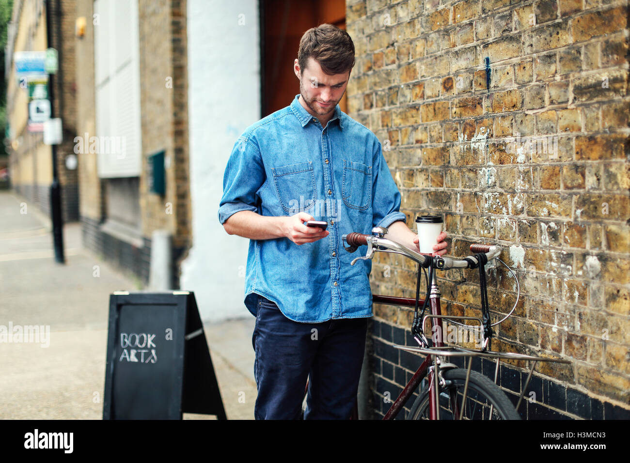 Young man holding coffee and checking mobile phone, with push bike leant against brick wall - Stock Image