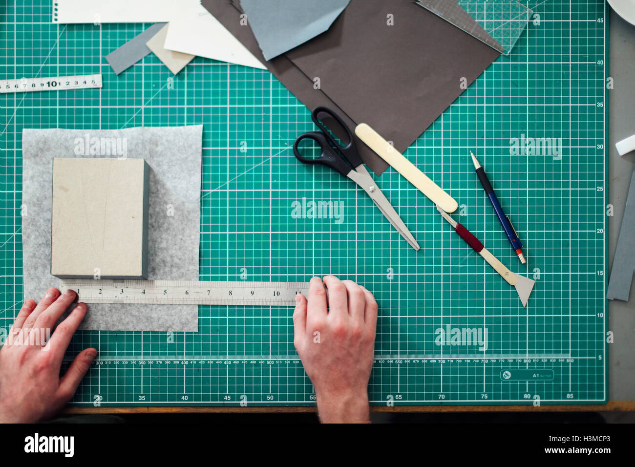 Overhead detail of hands, paper, cutting mat, ruler, scalpel and scissors in print studio - Stock Image