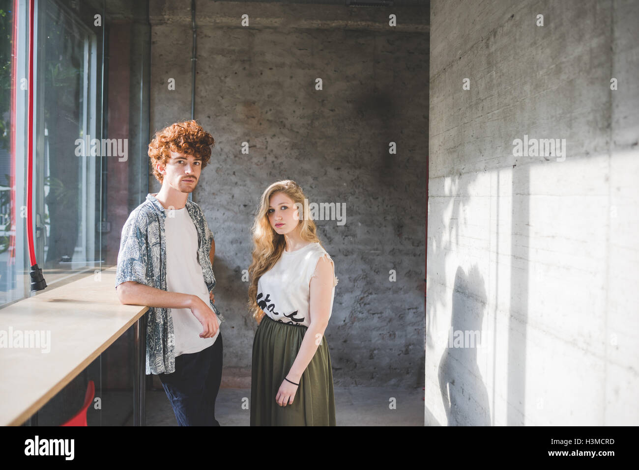 Co-workers beside bar counter by window - Stock Image