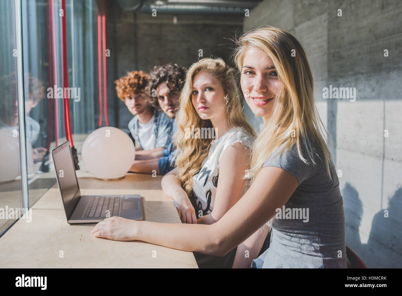 Co-workers working on laptop beside bar counter by window - Stock Image