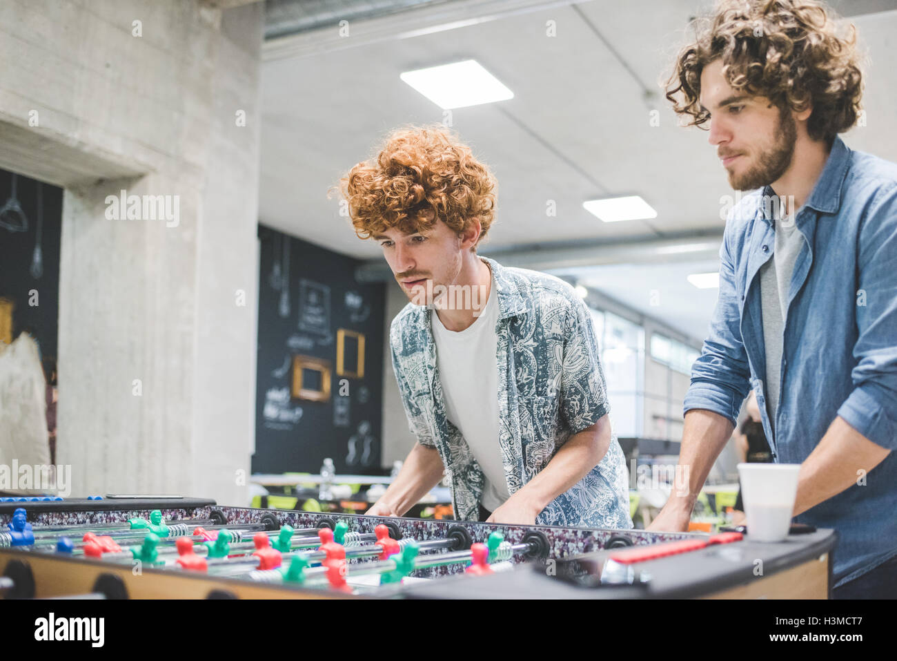 Co-workers playing foosball at break - Stock Image